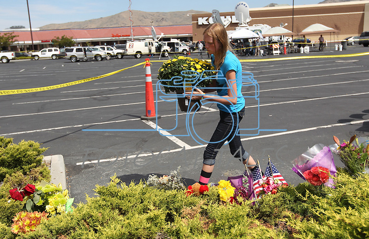 Adrianna White, 14, leaves flowers outside the IHOP restaurant in Carson City, Nev., on Wednesday, Sept. 7, 2011, following Tuesday's shooting spree that left five dead and seven injured. (AP Photo/Cathleen Allison)