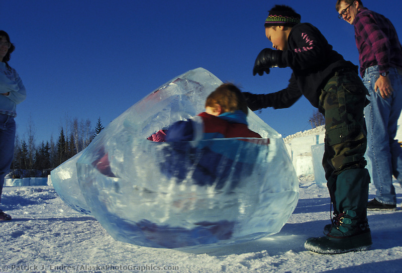 Children play in the spinning tear drops made from ice at the kiddie park at the World Ice Sculpting competition, Fairbanks, Alaska.