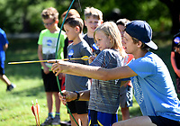 NWA Democrat-Gazette/DAVID GOTTSCHALK Stephen Angier, camp counselor with Kanakuk Kamps KampOut! Day Camp, helps Tristan Jones, 7, with the placement of an arrow Tuesday, June 25, 2019,during archery practice at the camp at Mount Sequoyah Center in Fayetteville. The camp offers five days of faith-based, day camp activities to children ages 5 to 12 years old. The activities included a zip line, inflatables as well as worship time and small group time with counselors.