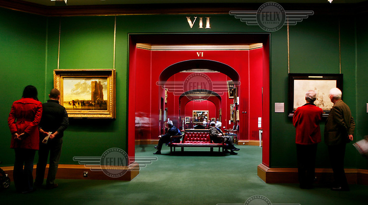 Visitors study paintings displayed in the National Gallery of Scotland in Edinburgh.
