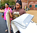 Britney Christian (right) holds items for incoming student Kai Lloyd of Chicago during freshman move-in day at Harris-Stowe State University in St. Louis on Wednesday August 15, 2018. At left is Zonnie Lloyd, mother of the new student.   Photo by Tim Vizer