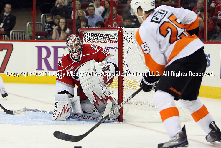 18 February 2011: Carolina's Cam Ward (30) watches Philadelphia's Matt Carle (25) handle the puck. The Carolina Hurricanes defeated the Philadelphia Flyers 3-2 at the RBC Center in Raleigh, North Carolina in a 2010-2011 regular season National Hockey League game.