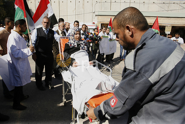 Palestinian medical staff stand next to a patient as she speaks to the media, calling on Egypt to open the Rafah crossing, in front of the Rafah border crossing in the southern Gaza Strip on November 6, 2014. Egypt closed the crossing into the Gaza Strip, the only route into the Palestinian territory not controlled by Israel, after Egyptian president Abdel Fattah al-Sisi declared a state of emergency on October 25, 2014, for three months, after the death of 30 soldiers in a suicide attack. Photo by Abed Rahim Khatib