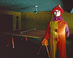 A one armed eight foot clown in an abandoned Hotel's game room with Ping Pong Table.