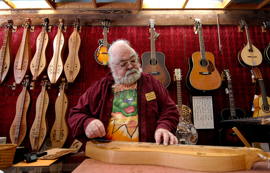 Former Mayor Bud Ford plays a dulcimer in his Manitou Springs store called The Dulcimer Shop. Michael Brands for The New York Times.
