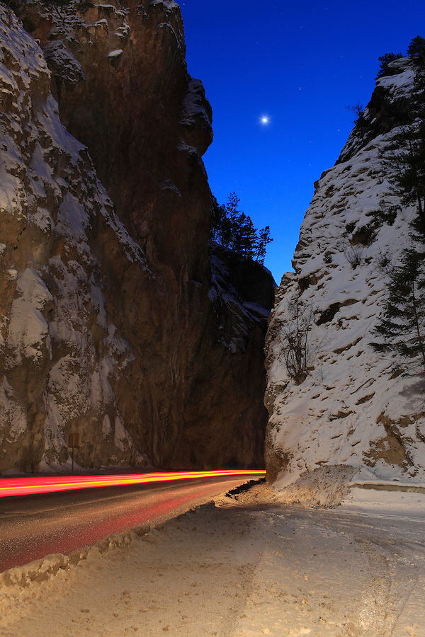 A long exposure captures streaking headlight and brake lights from cars passing down the narrow canyon roadway in the winter near Radium hot springs in British Columbia, Canada.