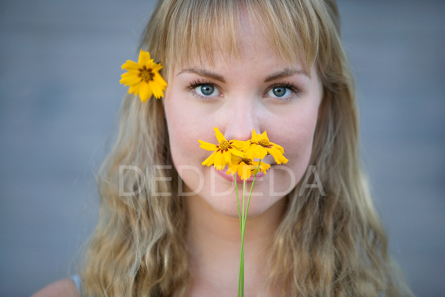 A beautiful blond young woman stands outdoors holding flowers in the summer.