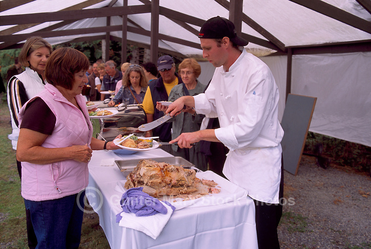 Chef carving and serving Roasted Pork at the Cowichan Valley Wine & Culinary Festival, on Vancouver Island, British Columbia, Canada