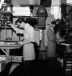 """Pittsburgh PA:  View of Brady Stewart Studio's darkroom at 725 Liberty Avenue.  Ross Catanza (left) is working at the 4""""x5"""" enlarger and Jim Garvey (right) is developing the prints. The big 8""""x10"""" enlarger in the background."""
