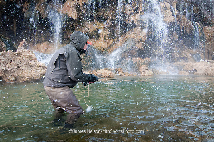 Mike Towler fly fishes for trout during a snow storm on the South Fork of the Snake River at the confluence of Fall Creek, Idaho.