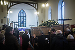 © Joel Goodman - 07973 332324 . 6 December 2013 . Marple , UK . The coffin is carried in to St Thomas's Parish Church for the service . The funeral of farmer Bob Watson . His son David Watson drives his father's coffin on a trailer hooked to the back of Bob's favourite tractor through Marple via Bob's local pub before taking it on to the church . Photo credit : Joel Goodman