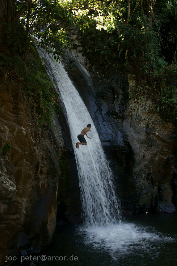 boy jumps down waterfall of Moni, island  Flores in archipelago of Indonesia