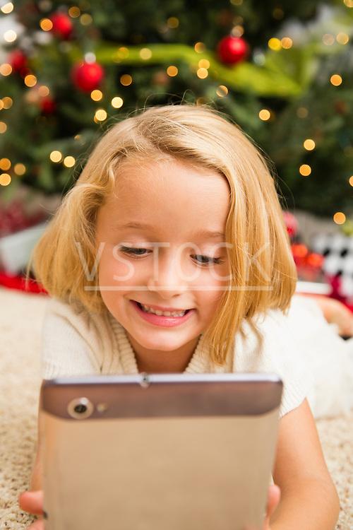 Girl (6-7) using digital tablet lying on carpet