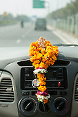 Uttar Pradesh, India. Agra to Delhi. Ganesh on dashboard with garland of marigolds.
