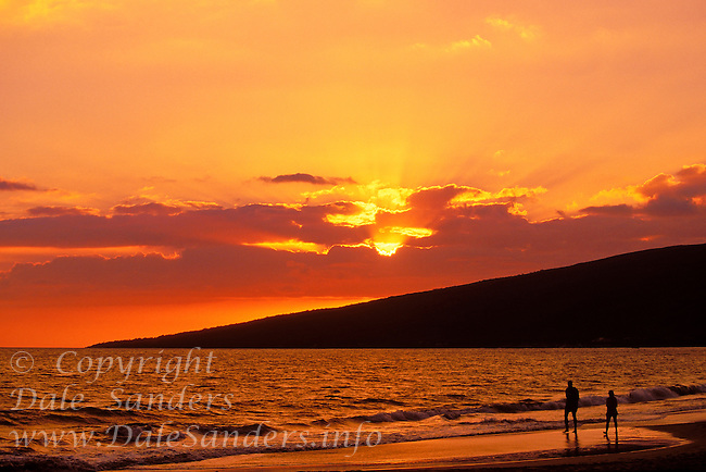 Couple walking along beach at sunset, Maui, Hawaii, USA.
