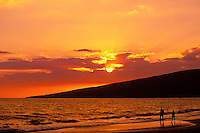 Couple walking along beach at sunset, Maui, Hawaii, USA.
