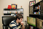 Emile Rosales, 23, makes a living playing video games. He says it isn't as easy as it sounds, though, because he has to record, edit, upload multiple videos to Youtube each week. He works in his Conyers, Georgia apartment, July 21, 2013.