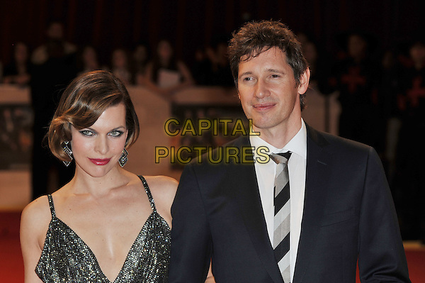 Milla Jovovich & Paul W.S. Anderson.'The Three Musketeers in 3D' world film premiere, Vue cinema, Westfield, London, England. 4th October 2011.half length black dress silver gold sparkly cowl neck smokey eyes red lipstick blue suit married husband wife  .CAP/MAR.© Martin Harris/Capital Pictures.