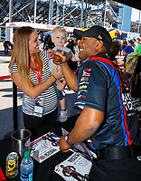 Mar 17, 2018; Gainesville, FL, USA; NHRA top fuel driver Antron Brown (right) greets a young fan during a Toyota hospitality appearance prior to qualifying for the Gatornationals at Gainesville Raceway. Mandatory Credit: Mark J. Rebilas-USA TODAY Sports
