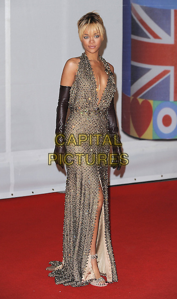 Rihanna (Robyn Rihanna Fenty).The Brit Awards 2012 arrivals, O2 Greenwich, London, England..21st February 2012.Brits full length gold bronze brown beige dress slit split long gloves halterneck leather beads beaded low cut plunging neckline cleavage .CAP/BEL.©Tom Belcher/Capital Pictures.