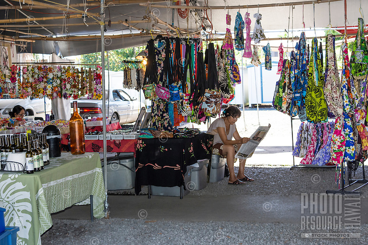 A local fabric vendor reads a newspaper at the Hilo Farmers Market on Mamo Street, Big Island of Hawai'i.