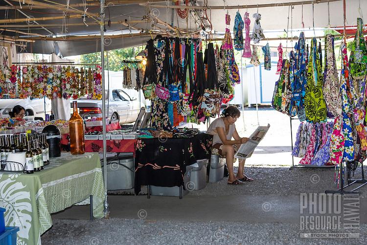 A local fabric vendor reads a newspaper at the Hilo Farmers Market on Mamo Street, Big Island of Hawai'i.