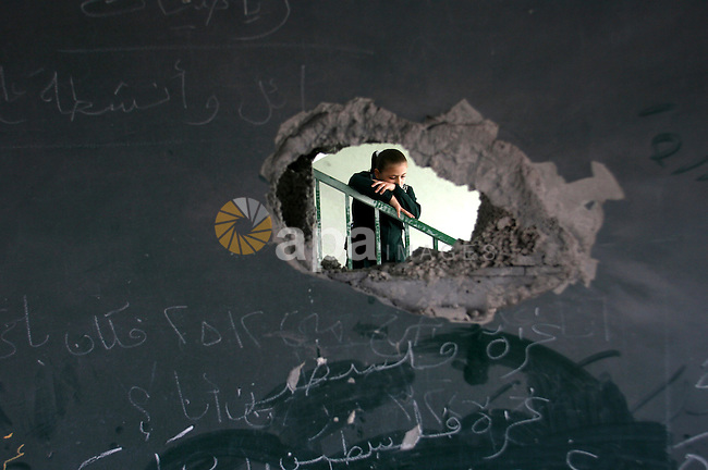 A Palestinian school girl appears through a hole in a wall in a damaged school in Rafah southern Gaza strip on November 26, 2012. The school was damaged some days ago, before a truce between Hamas and Israel ended eight days of cross border attacks in which 166 Palestinians and six Israelis died. Photo by Eyad Al Baba