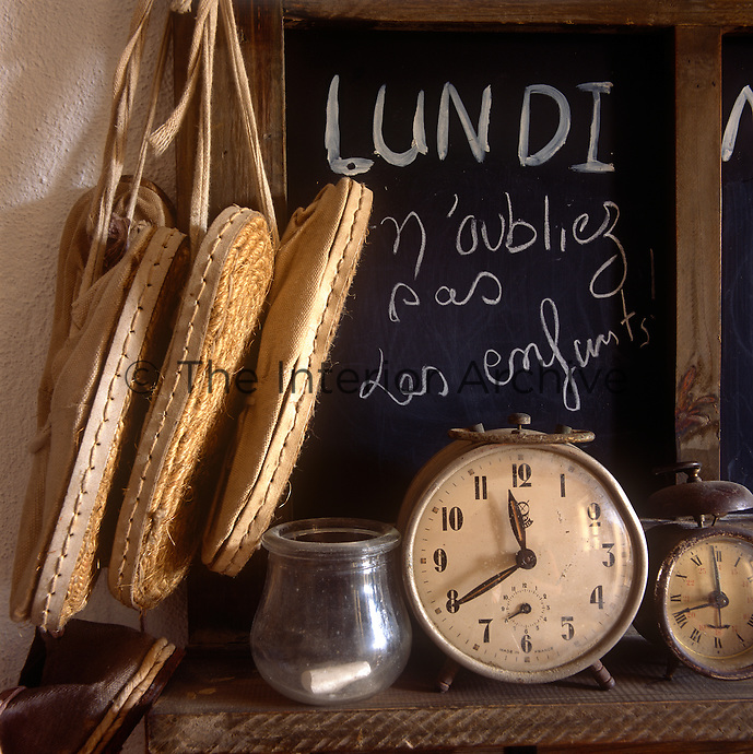 Vintage clocks are placed in front of a chalkboard marked with French writing. Three pairs of espadrills hang next to it.