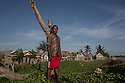 "Indonesia – Sumatra – Aceh - Suak Indrapuri – Masyudin, 54-years-old standing next to his seaside house, less than 30 meters away from the sea. ""Fifty years ago, the sea was two kilometres away"" he says in awe. But the constant coastal abrasion and the 2004 tsunami have eaten so much land, that the entire village has to be protected by a sea wall of sandbags and concrete. ""If I could, I would relocate to another village far from the sea. But I have no choice, my land is here"" he continues. A former fisherman, Masyudin lost his entire family in the tsunami: his wife, three children, one sister-in-law and a nephew. While his house and family were swept out by the wavers, Masyudin managed to save himself by climbing on the roof of the local market. When he went back home, only two buildings were still standing and corpses were everywhere."