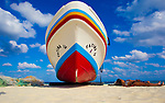 A fishing boat stands beside a pair of sunbathers on the beach in Playa del Carmen, Mexico.