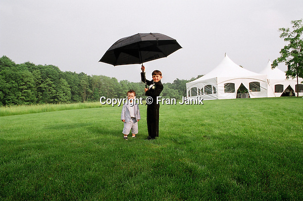Two young boys enjoy a wet day while attending a wedding in a field in southern Vermont.