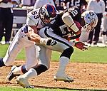 Oakland Raiders vs. Denver Broncos at Oakland Alameda County Coliseum Sunday, September 20, 1998.  Broncos beat Raiders  34-17.  Denver Broncos linebacker Bill Romanowski (53) tackles Oakland Raiders running back Harvey Williams (22).