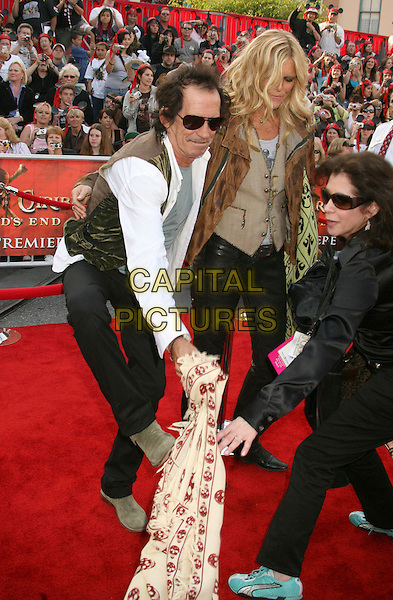 "KEITH RICHARDS & PATTI HANSEN .""Pirates Of The Caribbean: At World's End"" World Premiere held at Disneyland, Anaheim, California, USA,.May 19th, 007.3 full length skull crossbones scarf black trousers pulling gesture waistcoat sunglasses shades married husband wife .CAP/ADM/RE.©Russ Elliot/AdMedia/Capital Pictures"