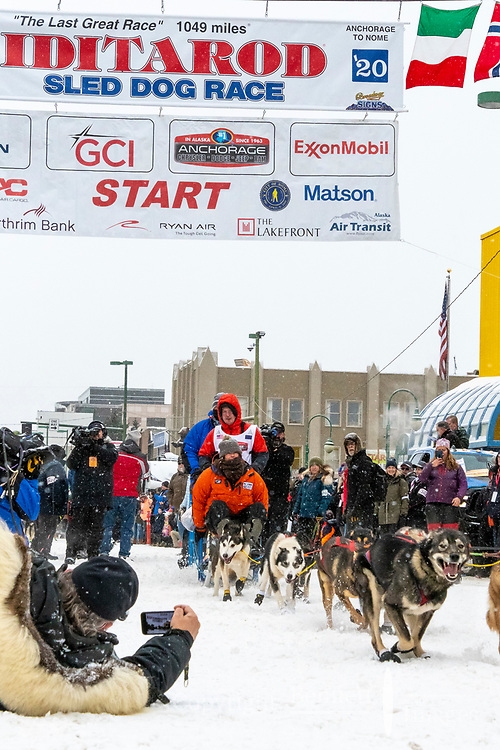Travis Beals and team leave the ceremonial start line with an Iditarider and handler at 4th Avenue and D street in downtown Anchorage, Alaska on Saturday March 7th during the 2020 Iditarod race. Photo copyright by Cathy Hart Photography.com