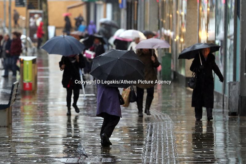 WEATHER PICTURE WALES<br /> Pictured: Shoppers defy the wet weather in Oxford Street, Swansea, south Wales.<br /> Re: Severe weather has been forecast for parts of the UK for the weekend.