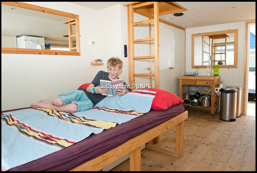 BNPS.co.uk (01202 558833)<br /> Pic: LauraDale/BNPS<br /> <br /> Cam McGregor, whose parents own the beach hut, lies on one of the two pull-out sofas and enjoys a book in the comfortable and spacious interior.<br /> <br /> A modest beach hut with no bathroom or mains electricity has gone on the market for a whopping 270,000 pounds - making it the most expensive in Britain.<br /> <br /> The asking price for the tiny wooden shack on Mudeford Spit near Christchurch, Dorset, is the same cost as a plush three-bedroom house in some parts of the country and is as much as a top-of-the-range Ferrari car.<br /> <br /> The 18ft by 12ft hut can sleep up to 12 people - four people on a mezzanine deck, four on two sofa beds and another two on a pull-out bed.<br /> <br /> The huge asking price is because it is just a stones throw away from the water boasting stunning sea views out towards the Isle of Wight and the Needles.<br /> <br /> The current owners are selling the beach hut so that they can move to another one on the same sandy strip with a different view.
