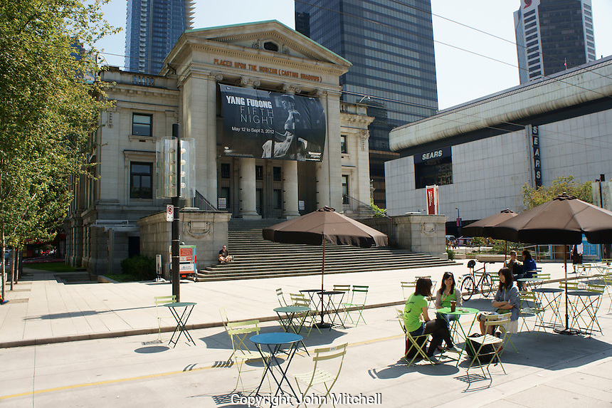 Young women relaxing in front of the Vancouver Art Gallery, Vancouver, British Columbia, Canada. This neoclassical building was formerly the Provincial Courthouse.