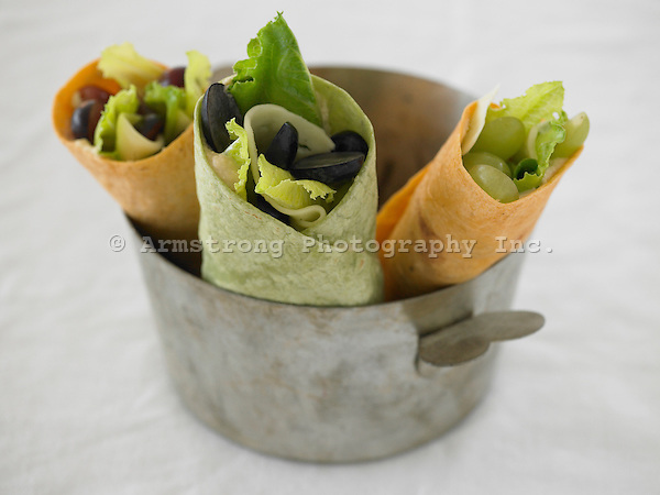 Hummus, lettuce, cheese, and grapes in red and green flour tortillas