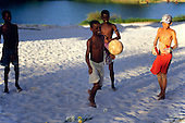Salvador, Brazil. Young boys playing football barefoot on the sand; Lagoa de Abaete.