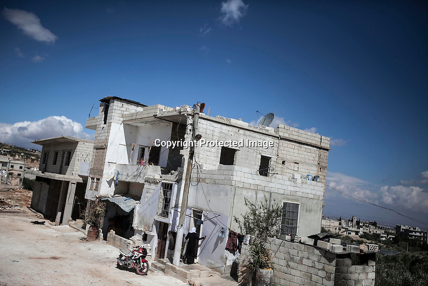 In this Thursday, Oct. 03, 2013 photo, a Syrian woman goes into her family house in Kafr Lata, a ghost village in a top of a mountain subdued under heavy shelling and bormbardments due the fighting between opposition fighters and government forces in the Idlib province countryside of Syria. (AP Photo)