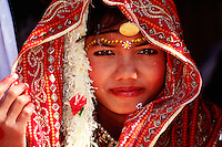 Portrait of a smiling young Indian girl in a red headpiece and painted forehead at a festival. Jaisalmer, India..