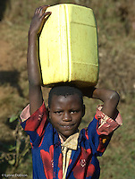 Sheila Irumua, 8, braces herself to carry a heavy jerry can of water she collected early that morning. She walked home with five other children who also were doing the same hard chore.