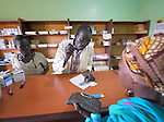 Angelo Ngor, a pharmacy assistant, explains the use of a medicine to a patient at the St. Daniel Comboni Catholic Hospital in Wau, South Sudan. Student Sophia Adul looks on.