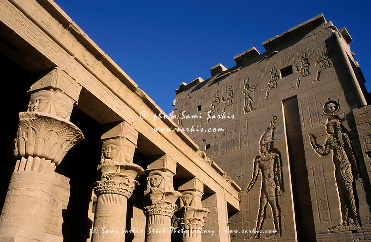 Stone walls depicting hieroglyphs and colonnade at the Temple of Isis First Pylon at Philae, Egypt.