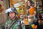 Apr. 30 - BANGKOK, THAILAND: A Thai soldier on security duty in front of a Haagen Daz ice cream shop in the Silom section of Bangkok Friday. The Red Shirts moved one of their barricades in the Sala Daeng Intersection in Bangkok Friday In one of the first positive moves to take place since the Red Shirts occupied central Bangkok in early April. The barricade was moved far enough back to open one lane of traffic on  Ratchadamri Street to allow ambulance access to King Chulalongkorn Memorial Hospital, a large hospital at the intersection. Many of the patients in the hospital have been moved to other hospitals because a group of Red Shirts entered the hospital Thursday looking for Thai security personnel, who were not in the hospital. The stand off between the Red Shirts and the government enters its third month in May. The Red Shirts continue to call for Thai Prime Minister Abhisit Vejjajiva to step down and dissolve parliament and demand the return of ousted Prime Minister Thaksin Shinawatra.   PHOTO BY JACK KURTZ
