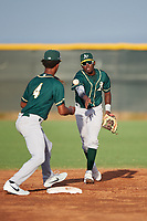 AZL Athletics Green second baseman Givaine Bisilia (1) flips a ball to shortstop Jalen Greer (4) to start a double play during an Arizona League game against the AZL Reds on July 21, 2019 at the Cincinnati Reds Spring Training Complex in Goodyear, Arizona. The AZL Reds defeated the AZL Athletics Green 8-6. (Zachary Lucy/Four Seam Images)