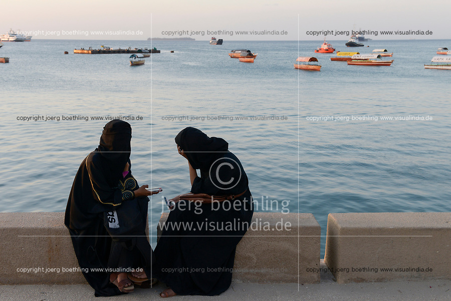 TANZANIA, Zanzibar, Stone town, two muslim women with smart phone at seafront
