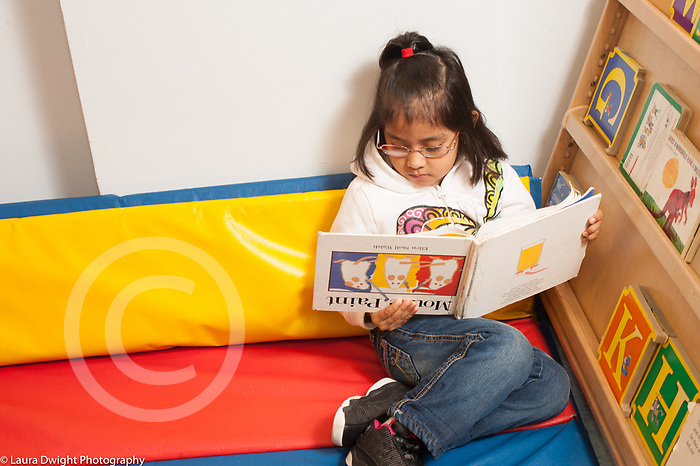 Education preschool 3 year olds girl sitting alone looking at picture book, holding it upside down