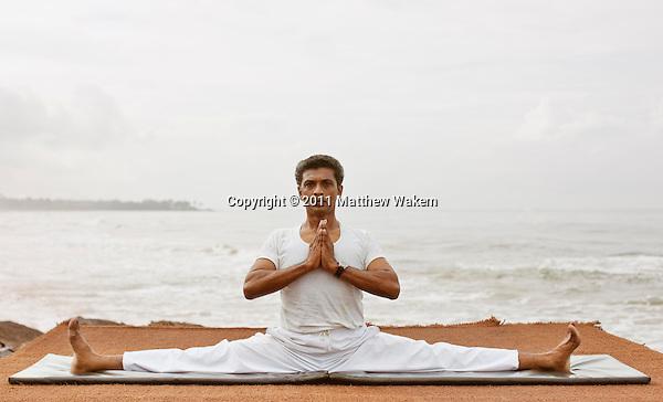 Sri Lankan yoga master practices yoga by the beach at Saman Villas, Aturuwella, Bentota, Sri Lanka; shown here is the seated wide-legged straddle pose (or upavistha konasana).