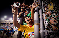 Polo Guitierrez (cq, in yellow) and Salvador Saldana (cq, in green) struggle to cheer and take pictures of the Mexican soccer team before Mexico played Colombia in an exhibition game at the Cotton Bowl in Dallas, Texas, USA, Wednesday, Sept., 30, 2009. Colombia won the game 2-1, which was played as the second game of a double header after an FC Dallas soccer game in an attempt by Major League Soccer to draw a new crowd of hispanic people to the sport in the US...PHOTOS/ MATT NAGER